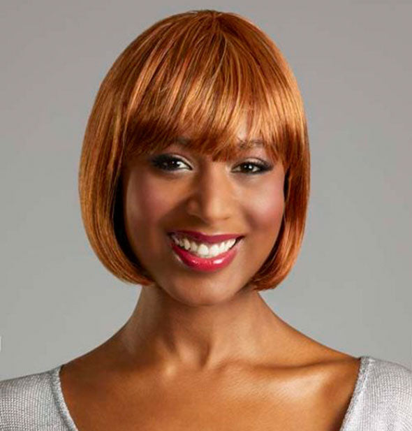 Model wearing a short, strawberry blonde wig with bangs.