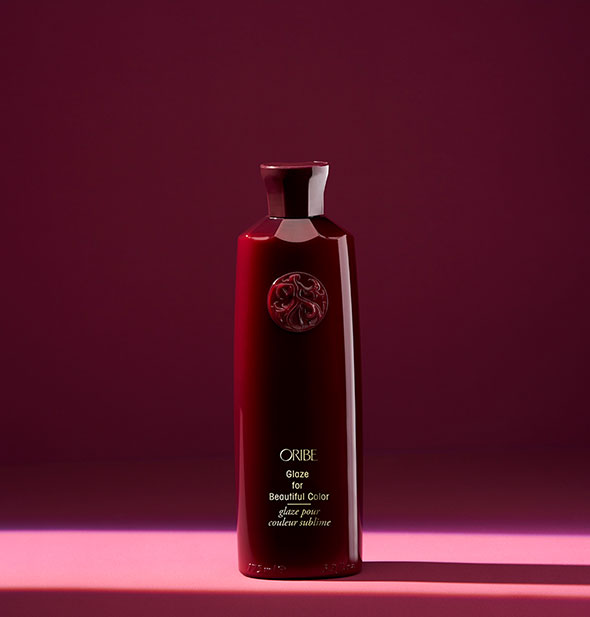 Red bottle of Oribe Glaze for Beautiful Color on red background