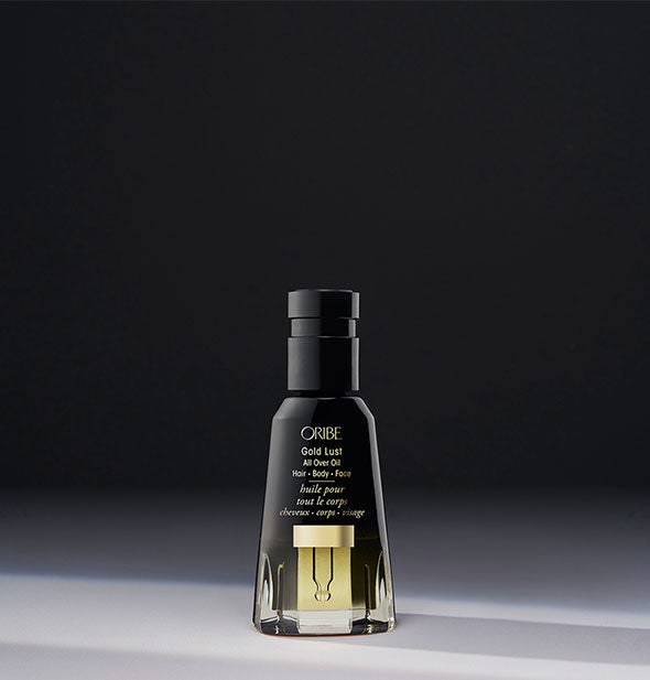 Black and gold bottle of Oribe Gold Lust All Over Oil on dark gray background