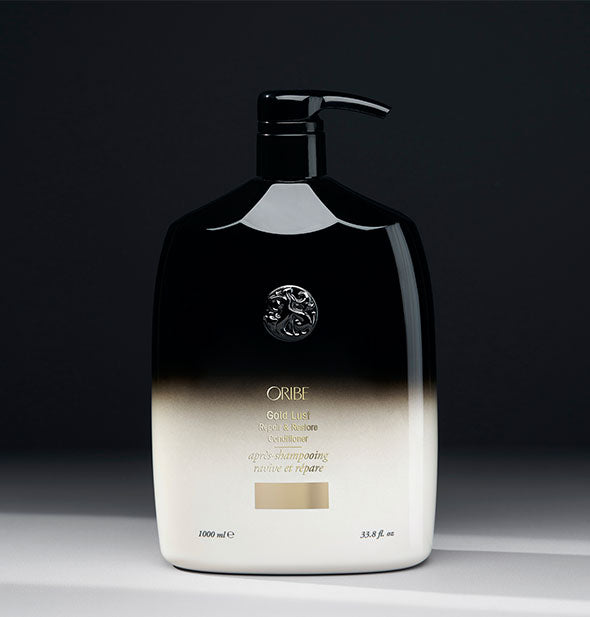 33.8 ounce black-to-white bottle of Oribe Gold Lust Repair & Restore Conditioner on gray background