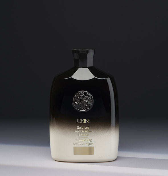 8.5 ounce black-to-white bottle of Oribe Gold Lust Repair & Restore Shampoo on gray background