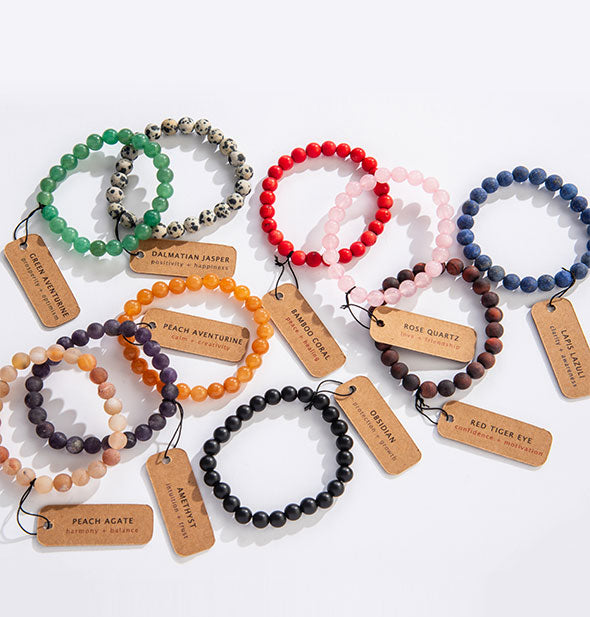 An arrangement of beaded bracelets in varying colors and stone types with corresponding labels.