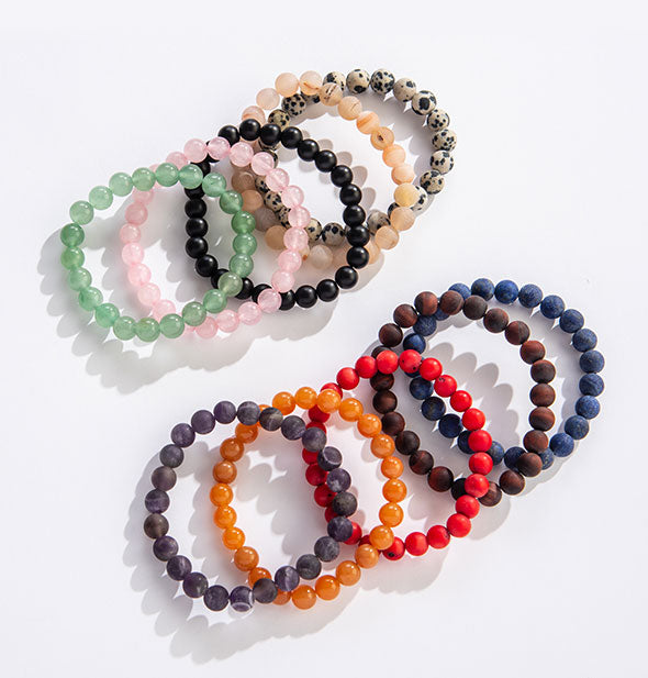 An arrangement of beaded bracelets in varying colors and stone types.
