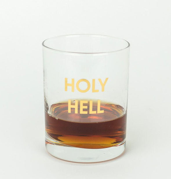 Holy Hell Rocks Glass partially filled with brown liquor.