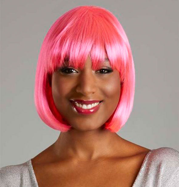 Model wearing a short, pink wig with bangs.