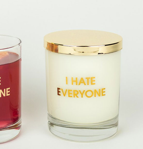 "Glass candle imprinted with the phrase, ""I Hate Everyone"" in metallic gold foil is covered with a gold lid."