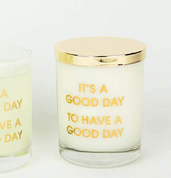 "A glass candle with gold lid and the phrase ""It's a Good Day to Have a Good Day"" printed in gold foil."