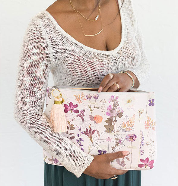 Model holds a large decorative floral pouch