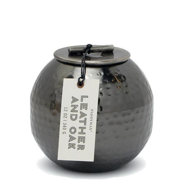 "Rounded, hammered black metal candle with rustic lid and hangtag that reads, ""Leather and Oak."""