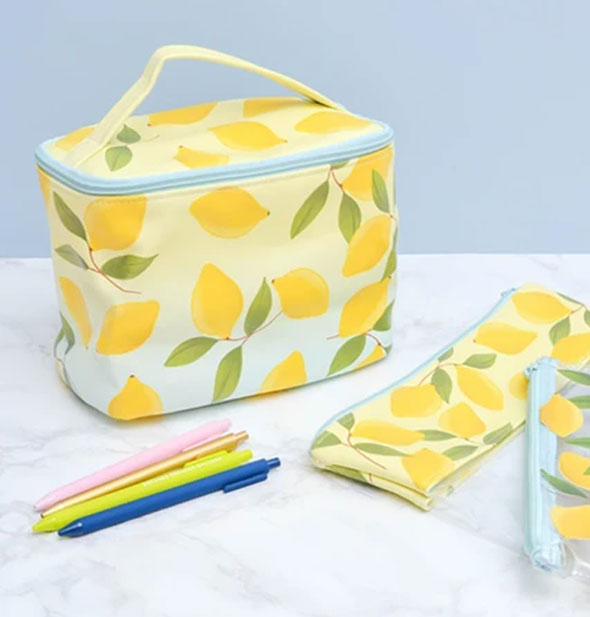 Lemon print pouches in different body styles on a marble surface with multicolored pens