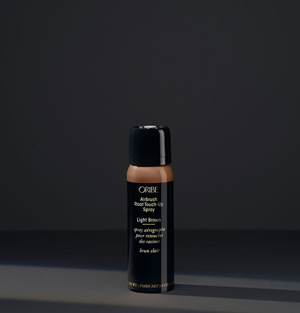 Small can of Oribe Airbrush Root Touch-Up Spray in the shade Light Brown on a dark background