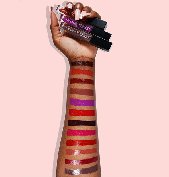 A person holding assorted 4 Ever + Ever Intense Lip Paint with swatches of the various shades shown on their arm