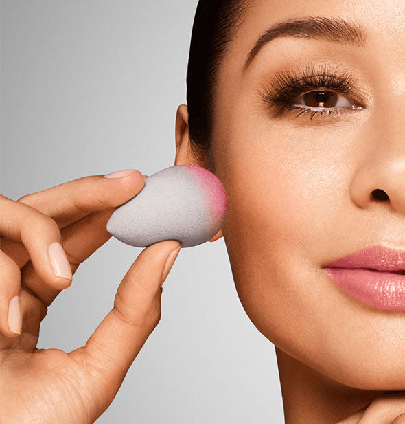 Model demonstrates application of blush with a BeautyBlender sponge