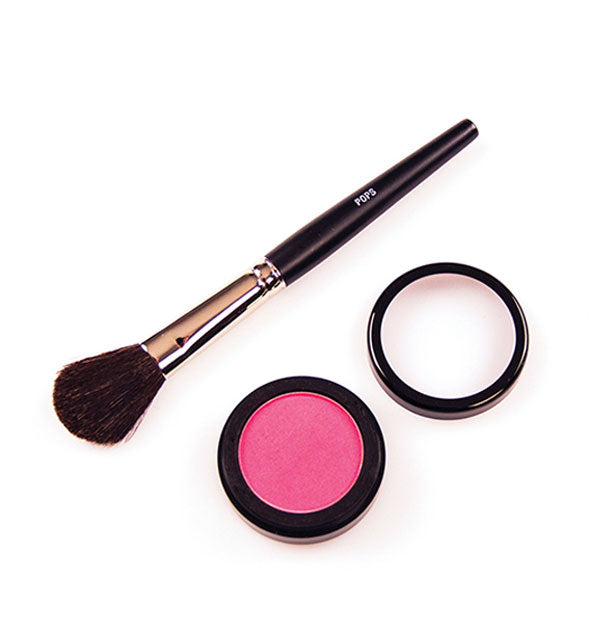 A blush brush next to a round blush compact with lid removed