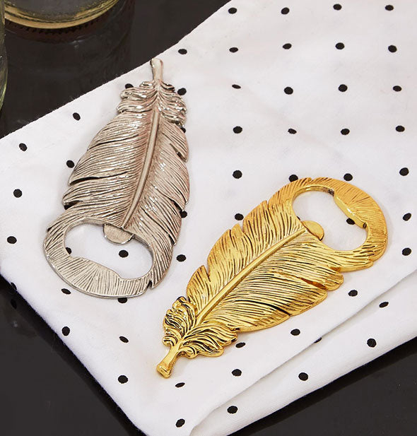 Two feather shaped bottle openers in silver and gold finishes