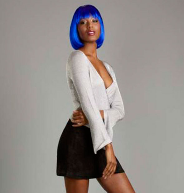 A model poses in black skirt and white shirt wearing a short, bob-style blue wig with bang fringe.