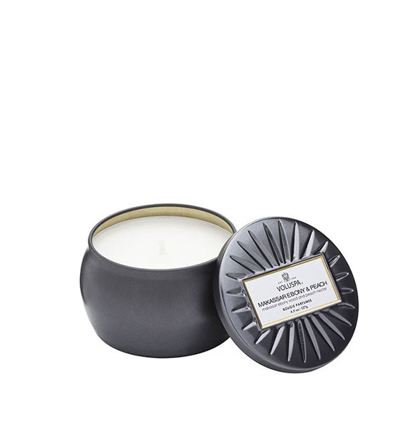 A small unlit candle inside a rounded tin with metallic matte black finish and matching embossed lid set to the side.