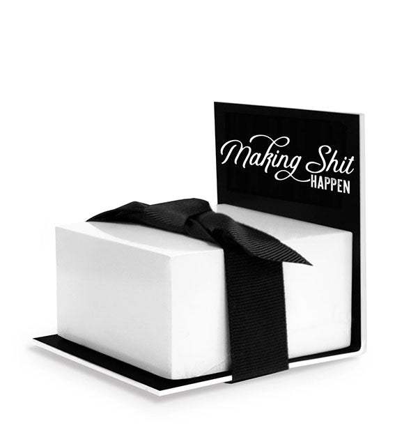"A stack of white sticky notes wrapped in a black bow sits on an acrylic display inscribed with the words, ""Making Shit Happen."""