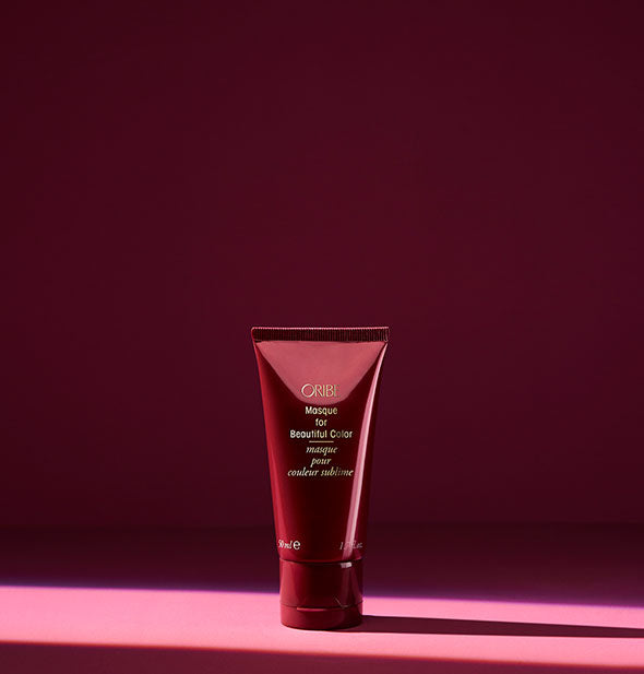 Small bottle of Oribe Masque for Beautiful Color on dark pink background
