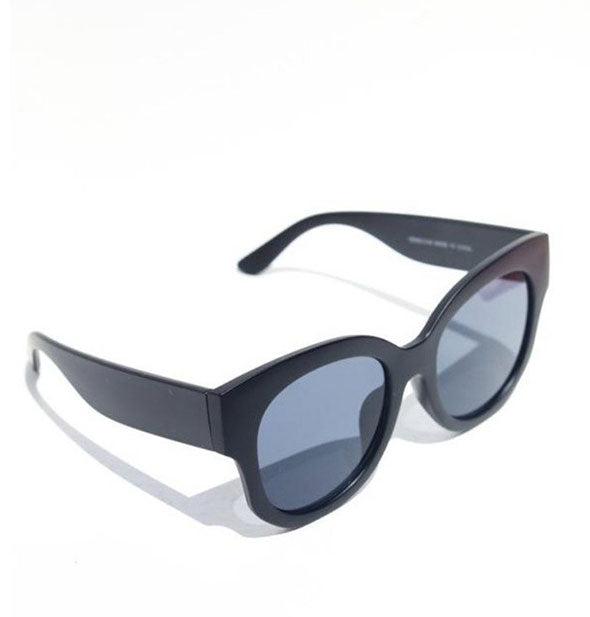 Three-quarter view of black sunglasses with blue-gray lens tint