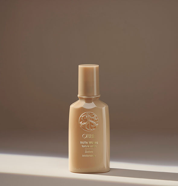Small gold bottle of Oribe Matte Waves Texture Lotion on a neutral background