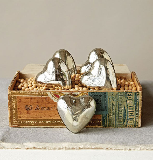 Collection of shiny metallic heart tokens in and around an antique cigar box