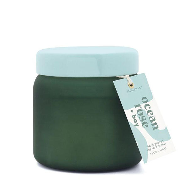 "Dark green glass candle jar with light aqua lid and hangtag that reads, ""Ocean Rose + Bay."""