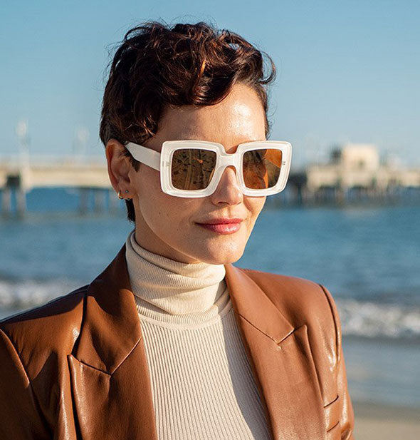 Model wears a pair of white square sunglasses with amber lens