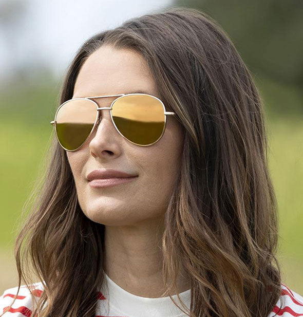 A model wears Peepers Heat Wave Polarized Sunglasses in Orange.
