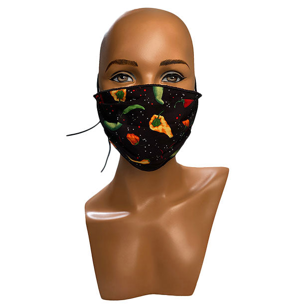 A mannequin head wears a face mask with pepper pattern