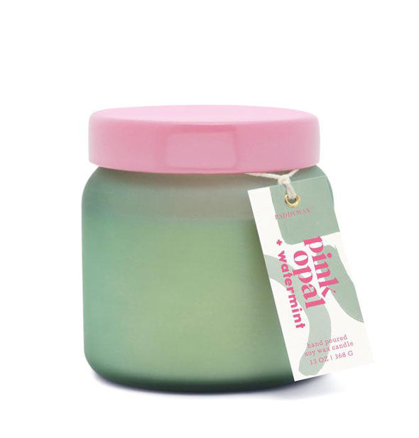 "Green glass candle jar with pink lid and hangtag that reads, ""Pink Opal + Watermint."""