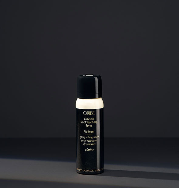 Small can of Oribe Airbrush Root Touch-Up Spray in the shade Platinum on a dark background