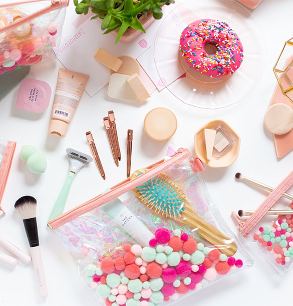 Clear plastic pouch with colorful embedded pom poms on a tabletop with an assortment of toiletries, makeup supplies, and a pink frosted donut with rainbow sprinkles
