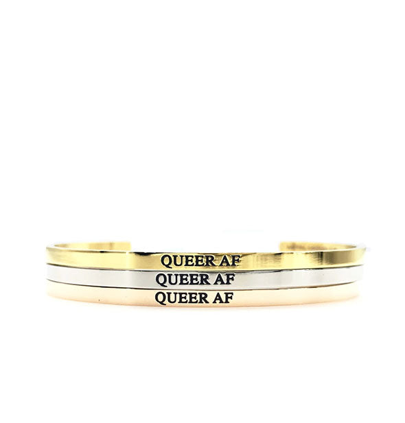 Three stacked Queer AF bangles in gold, silver, and rose gold
