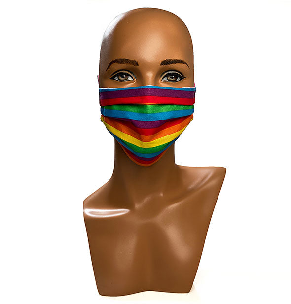 A mannequin head wears a rainbow patterned face mask