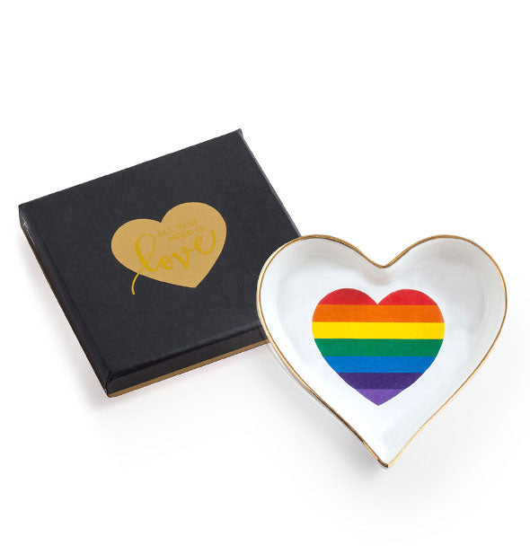 White heart-shaped dish with gold edge and rainbow heart design next to a black gift box with gold heart stamp