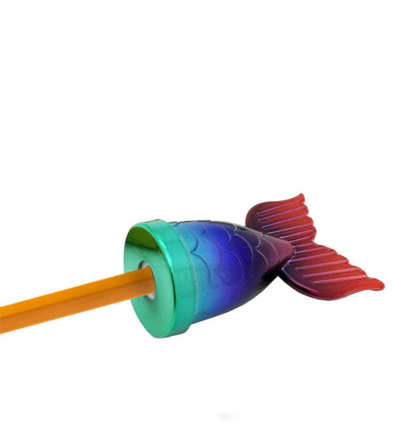 A pencil is inserted into a rainbow-colored, slightly metallic sharpener shaped like a mermaid's tail.