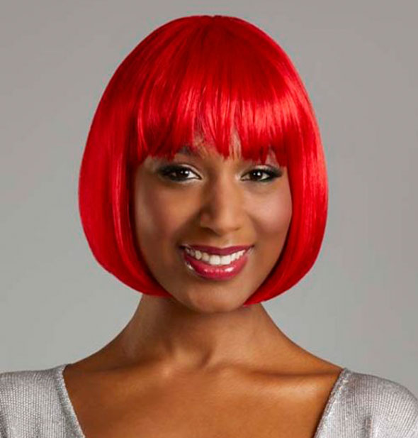 Model wearing a short, bright red wig with bangs.