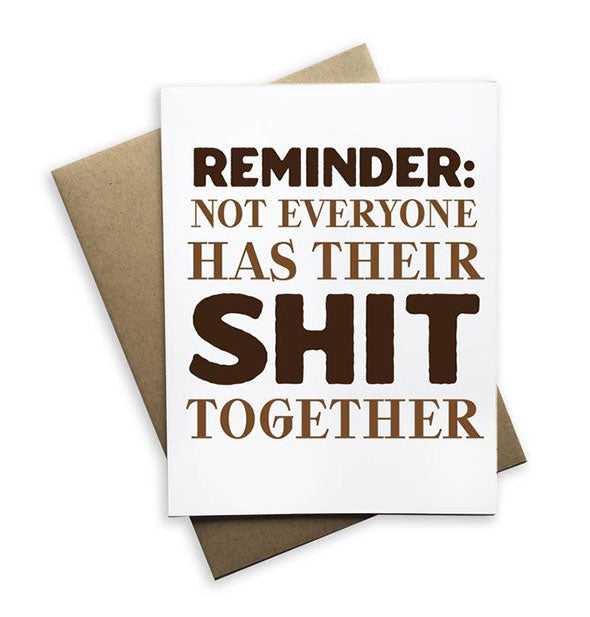 "White greeting card printed with the message, ""Reminder: Not Everyone Has Their Shit Together"" in dark brown ink rests on top of a kraft paper envelope."