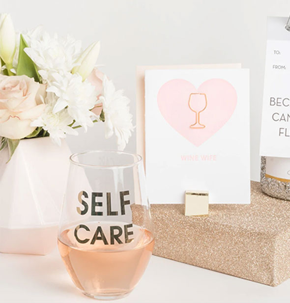 The Self Care Stemless Wine Glass is partially filled with rosé and staged among other Chez Gagné merchandise.
