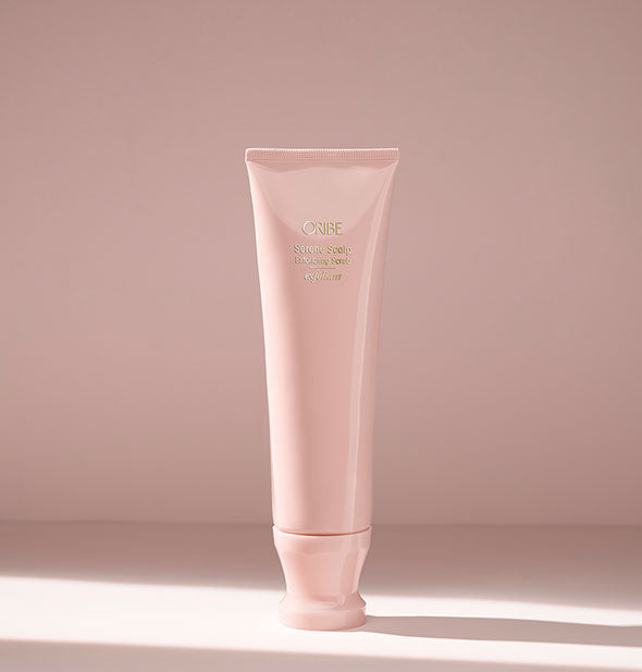 Light pink tube of Oribe Serene Scalp Exfoliating Scrub on blush background