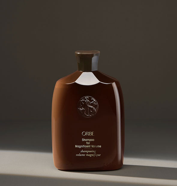 Brown bottle of Oribe Shampoo for Magnificent Volume on dark neutral background