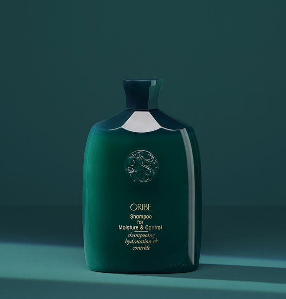 Teal bottle of Oribe Shampoo for Moisture & Control on teal background