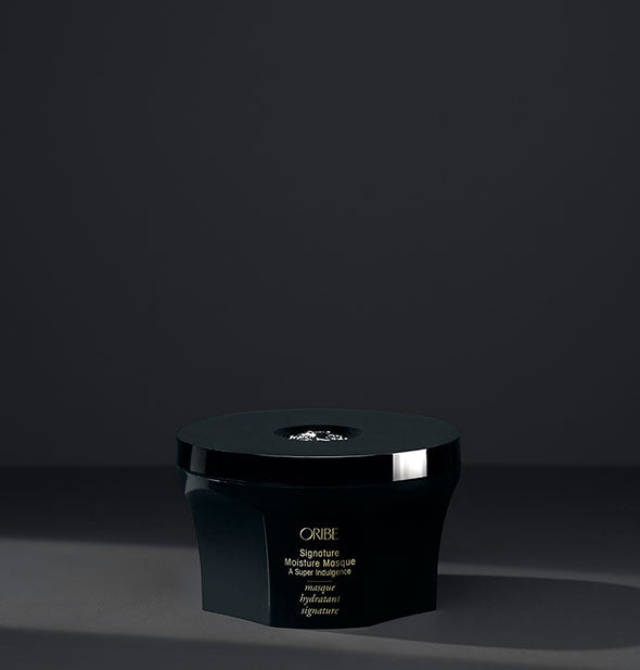 Black pot of Oribe Signature Moisture Masque on a dark gray background