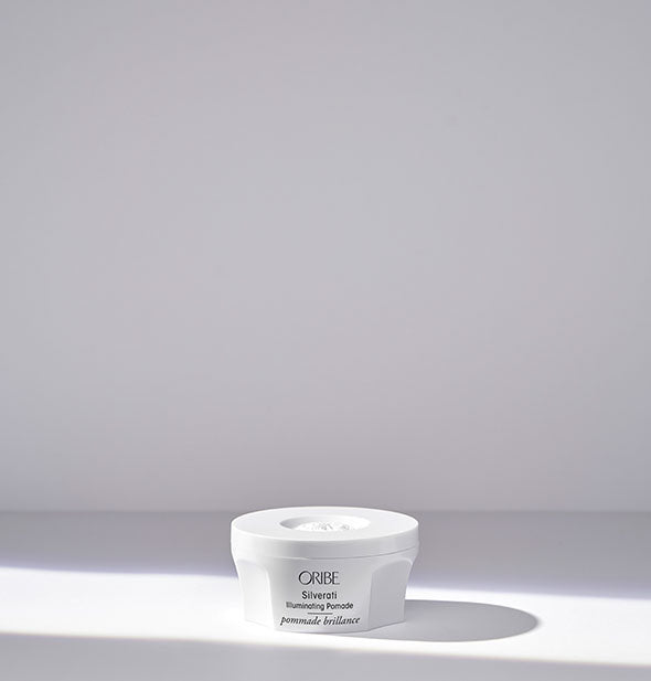 Small white pot of Oribe Silverati Illuminating Pomade on light gray background