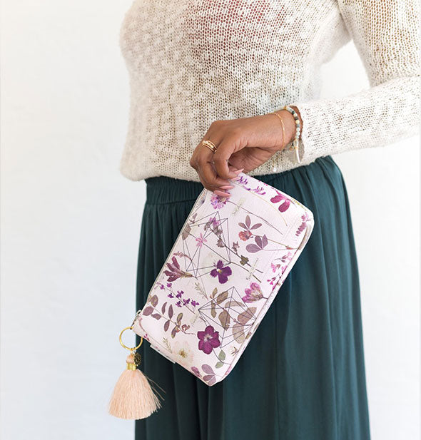Model holds a small floral pouch with peach tassel