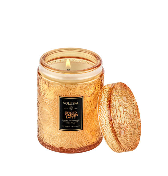 Burning candle in an orange embossed glass jar container with black label and matching lid set to the side.