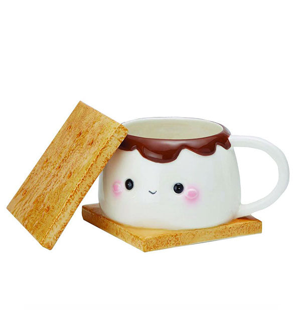 "A mug that's designed to resemble a smiling s'more is shown with its ""graham cracker"" lid removed."