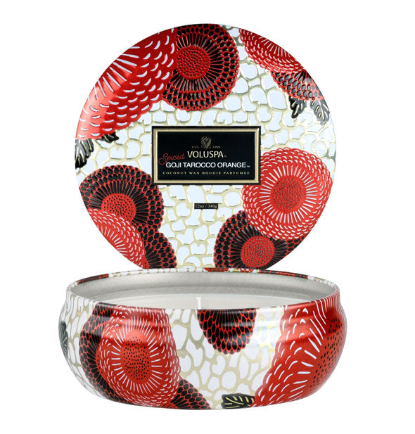 Decorative tin candle with black, red, and white floral pattern