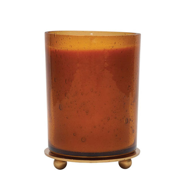 Amber glass jar candle with lid used as a footed coaster